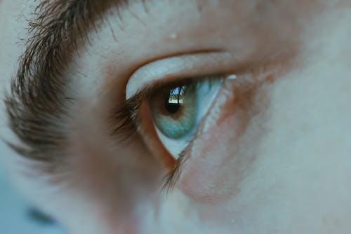 Green eye of crop unrecognizable woman
