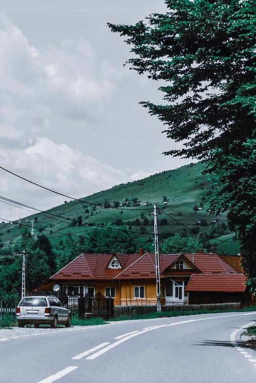 Residential house and car at roadside in mountainous countryside