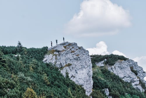 Group of anonymous tourists taking photos on rough cliff covered with moss near lush green trees under cloudy sky in summer