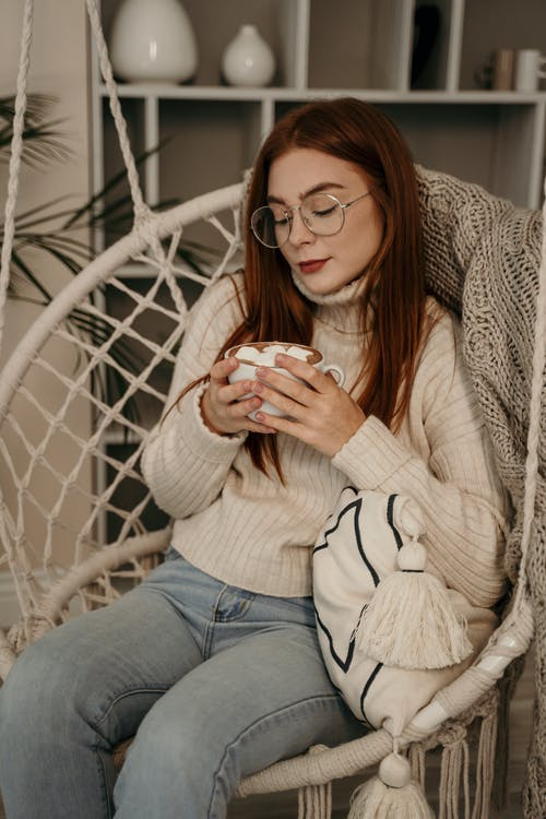 Woman in White Sweater and Blue Denim Jeans Sitting on White Metal Chair
