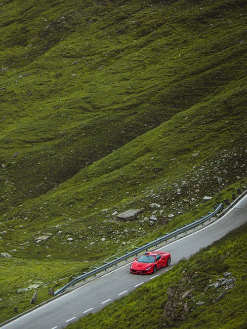 From above of red sports car driving along asphalt road in green grassy valley in daytime