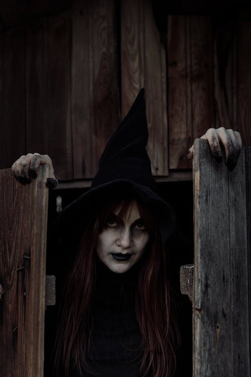 Witch Holding Wooden Doors
