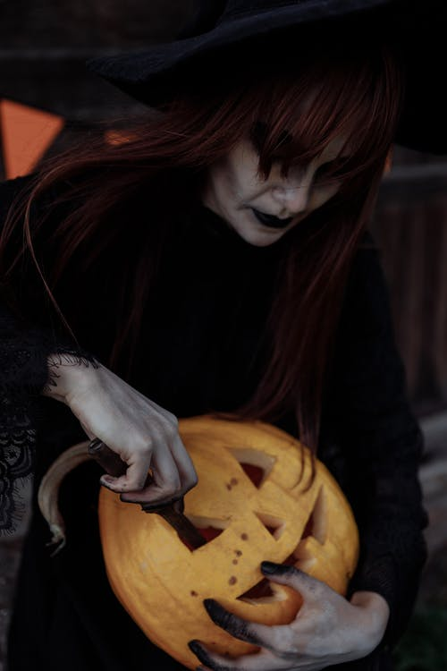 Witch Carving a Pumpkin