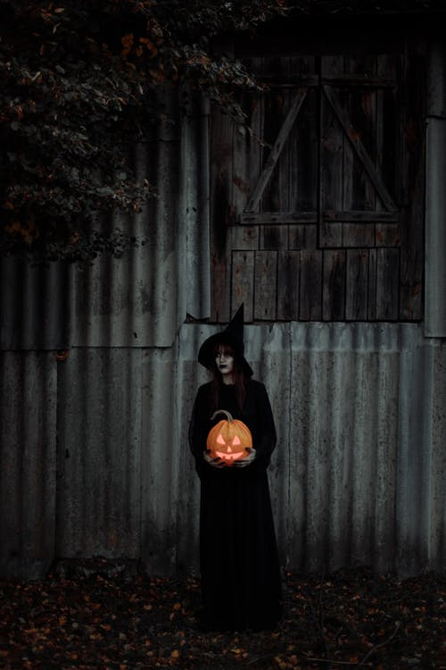 Witch Standing With a Pumpkin in Her Hands