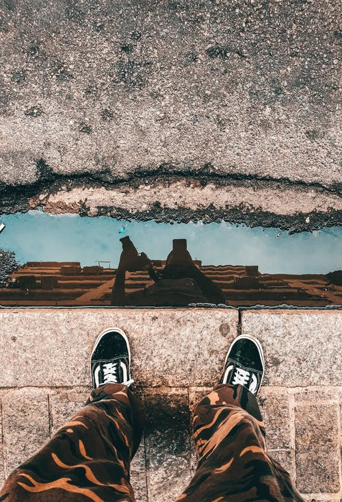 From above of crop anonymous person in trendy outfit taking selfie in puddle reflecting modern building and blue sky