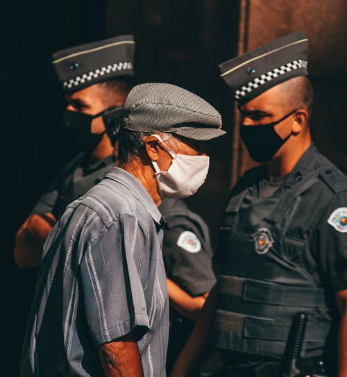 Anonymous ethnic policemen and senior male in medical masks on street