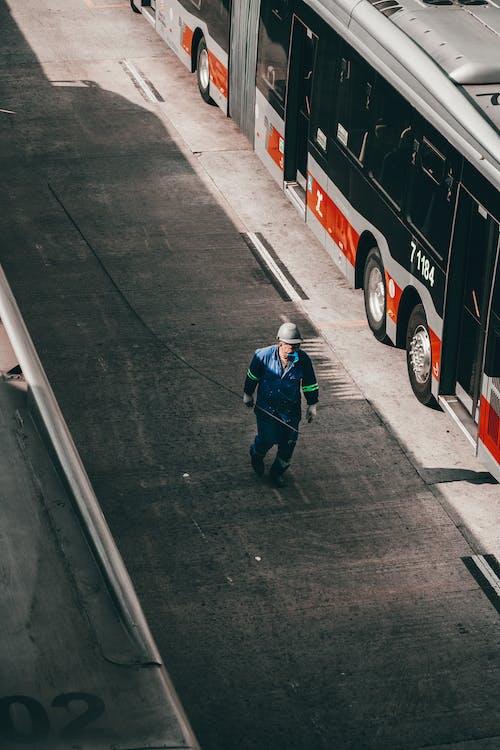 Anonymous male worker in uniform walking along street near bus station