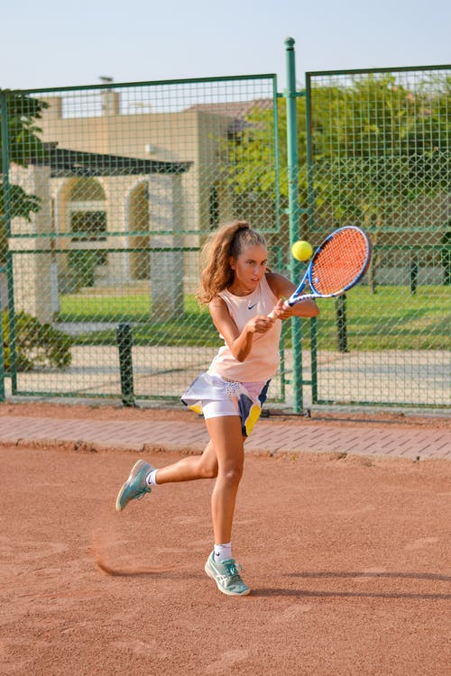 Sporty female playing tennis on court