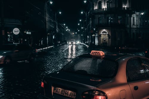 Taxi placed on street in rainy evening