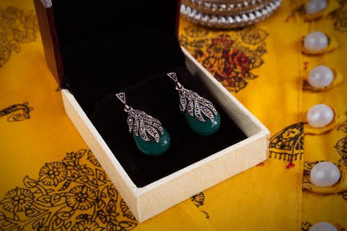 Silver Earrings with Green Gemstones on White Jewelry Box