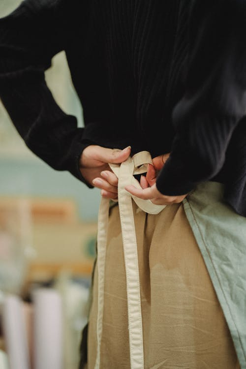 Crop faceless woman tying up apron laces