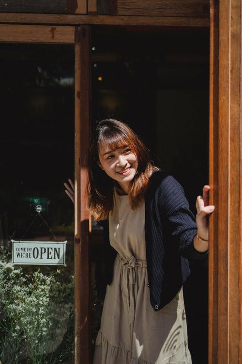 Smiling Asian woman in apron opening store door