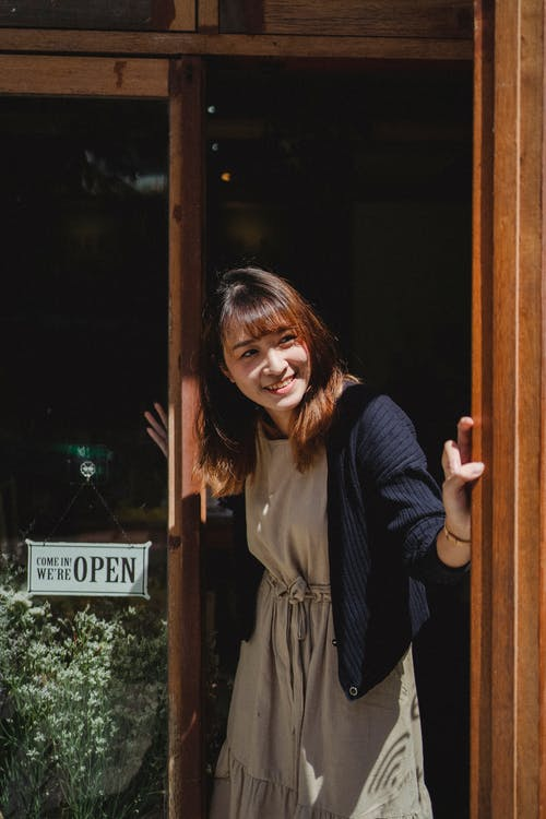 Positive smiling Asian female store worker opening store door and looking away contentedly
