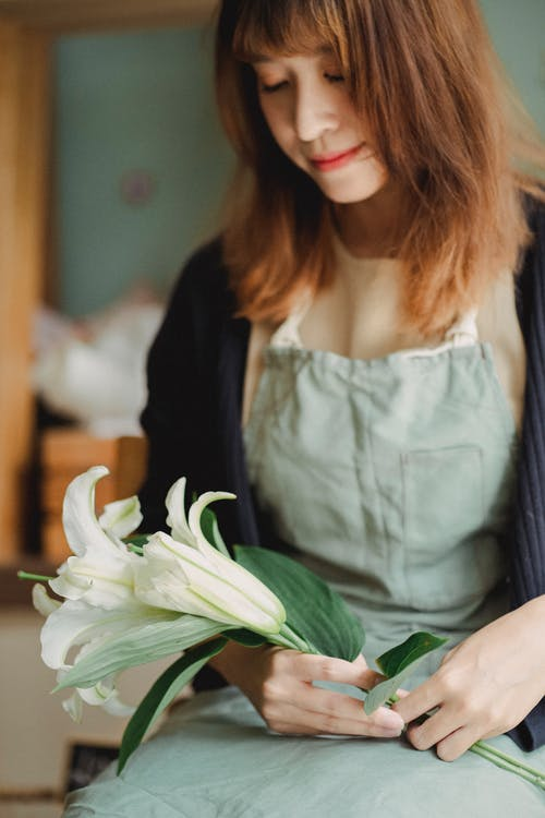 Crop serene Asian female florist sitting with white lily flower