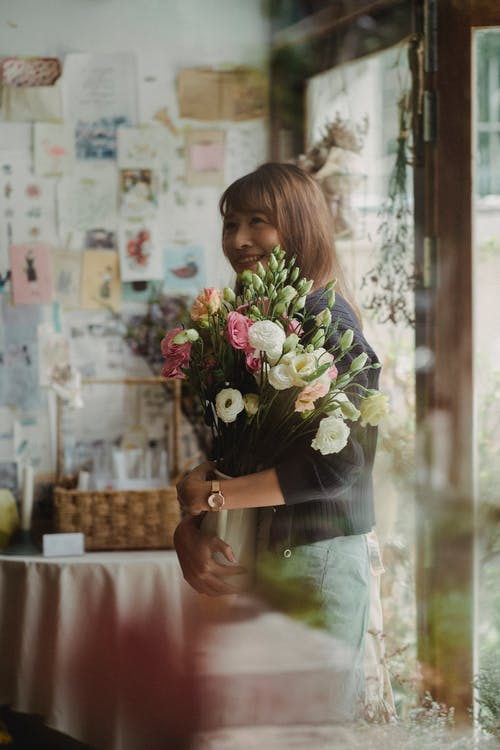 Cheerful ethnic woman standing with bouquet of flowers