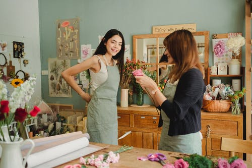 Positive florist getting ready for work in floral store