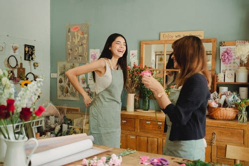 Laughing young female florist preparing for work on workshop