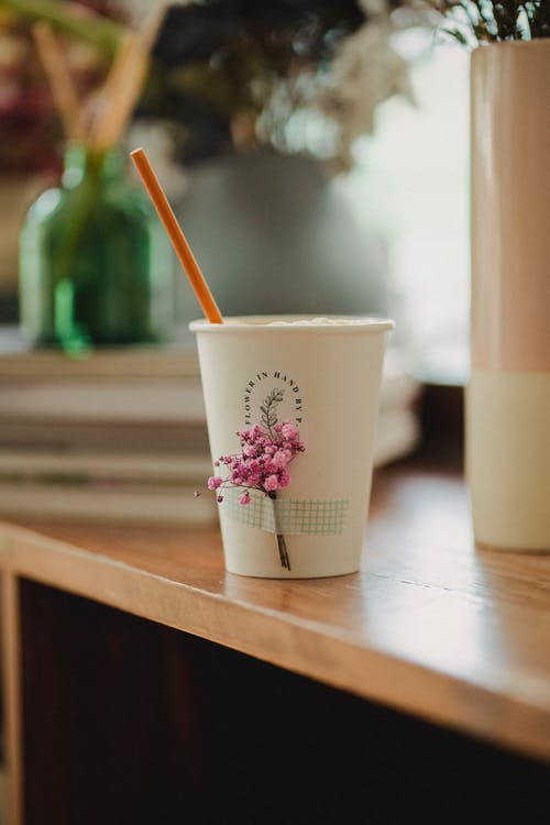 Small white cup decorated with flowers placed on wooden table near vases with flowers