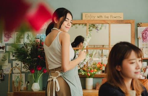 Smiling florist making bouquet in stylish shop