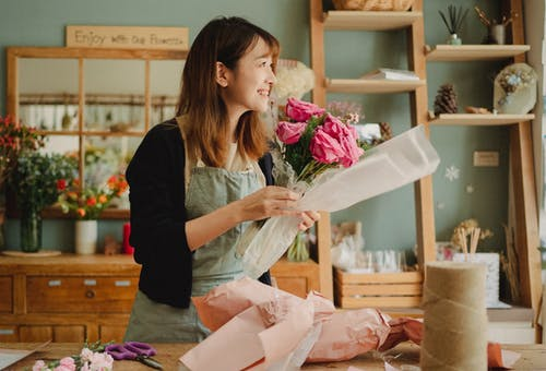 Optimistic Asian female florist wearing apron making flower bouquet with roses while standing in floral workshop