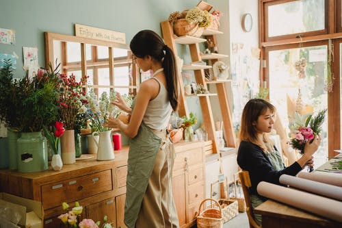 Concentrated diverse women making flower compositions in floral market