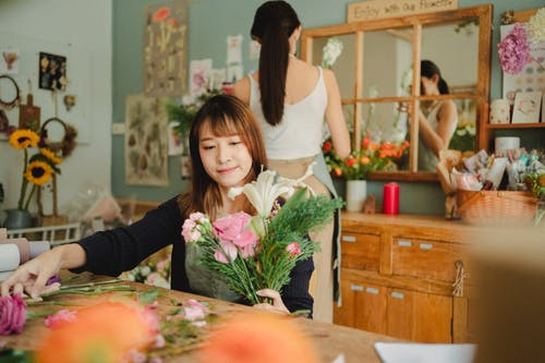 Focused ethnic florist making bouquet with fresh flowers