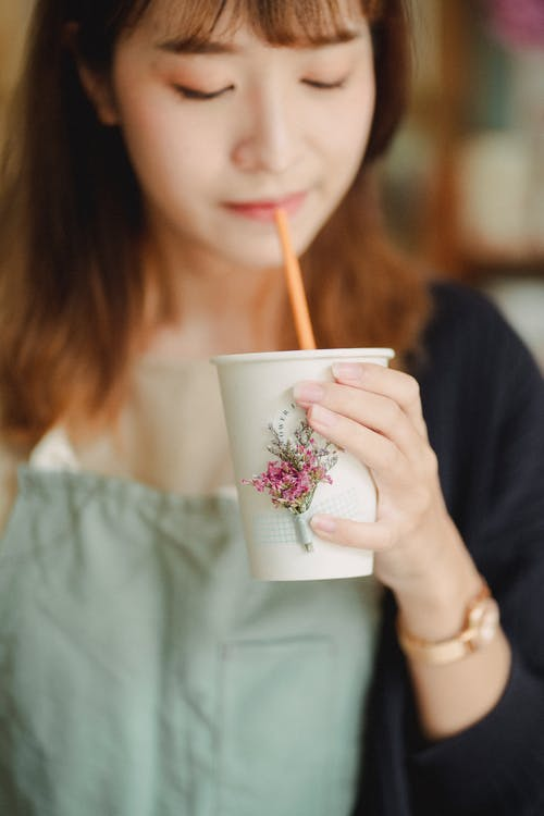 Crop Asian female in apron enjoying tasty drink in cup decorated with flowers while taking brake in work