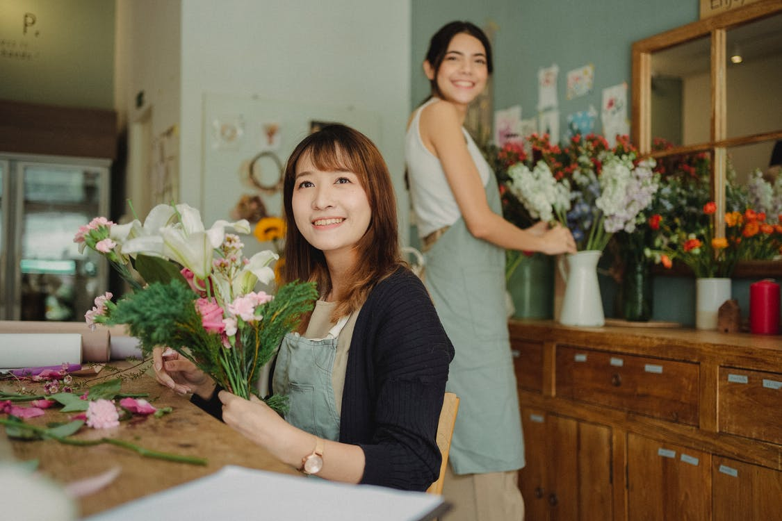 Happy Asian florist making bouquet with assistant