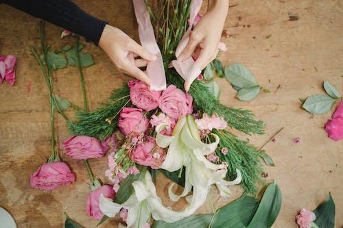 Florist tying ribbon on bouquet of flowers