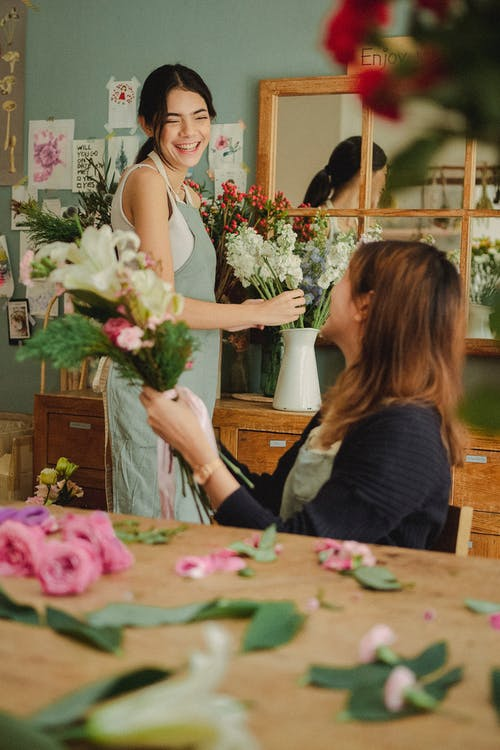 Side view of glad colleagues preparing blooming floral decorations while working in stylish florist workshop