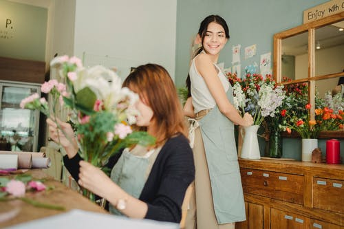 Cheerful florist preparing floral decoration in vase in workshop