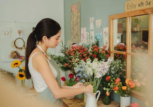 Woman preparing floral bouquet in floral shop