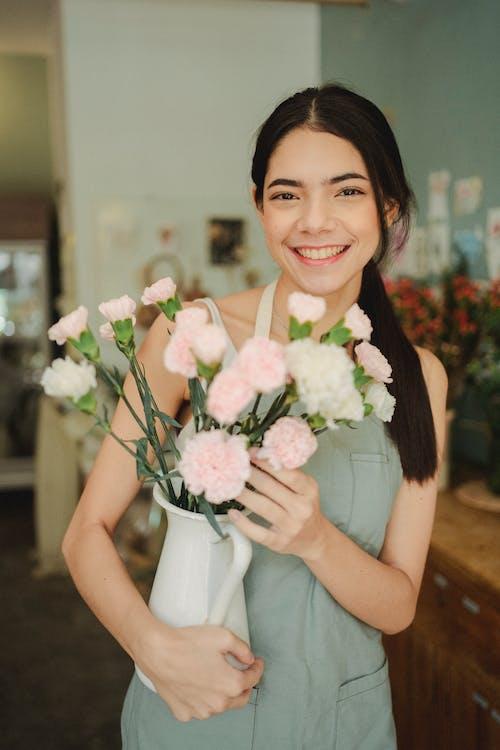 拿著有花的愉快的婦女花瓶