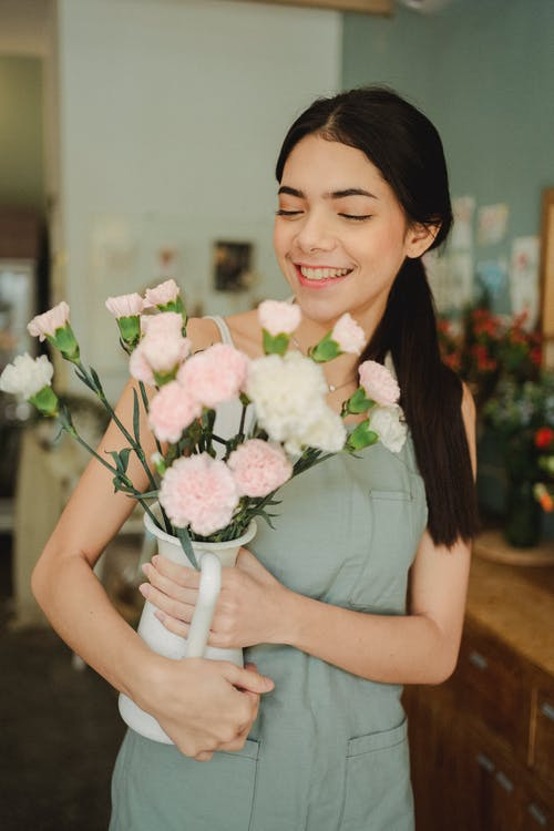 Young female florist with dark hair in apron holding vase with flowers and smiling during work day