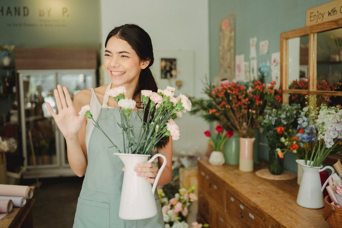Woman holding vase with flowers in shop