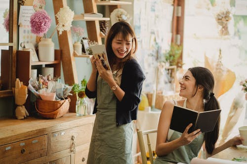 Cheerful women working together in floral shop