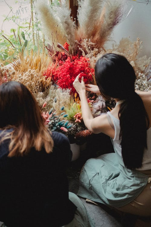 Faceless women choosing flowers for bouquet