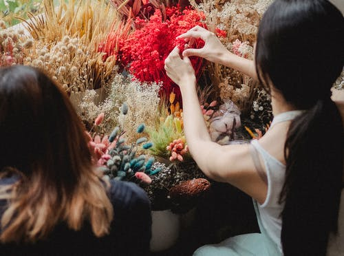Crop women arranging bouquets in shop
