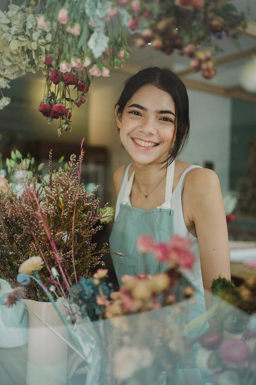 Cheerful young florist in shop