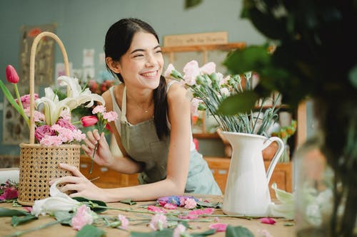 Young happy ethnic woman with blooming flowers in wicker basket looking away at table in shop