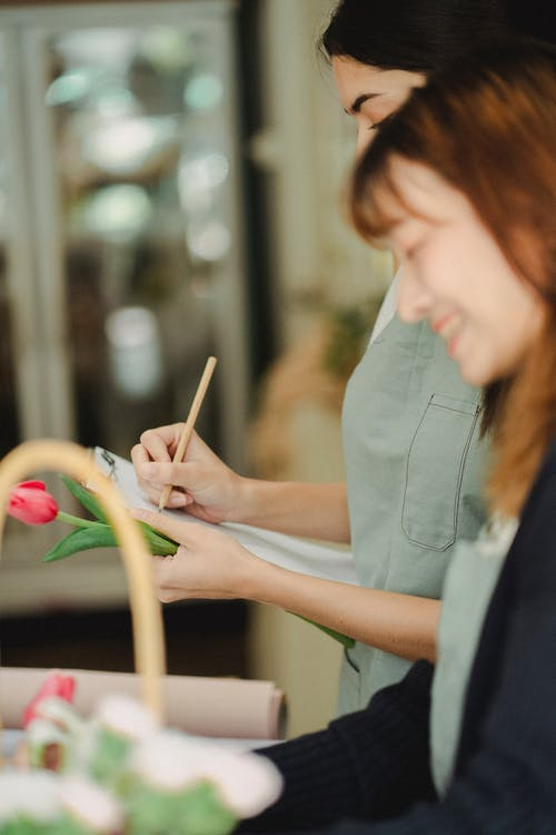 Unrecognizable multiracial women with clipboard in floral shop
