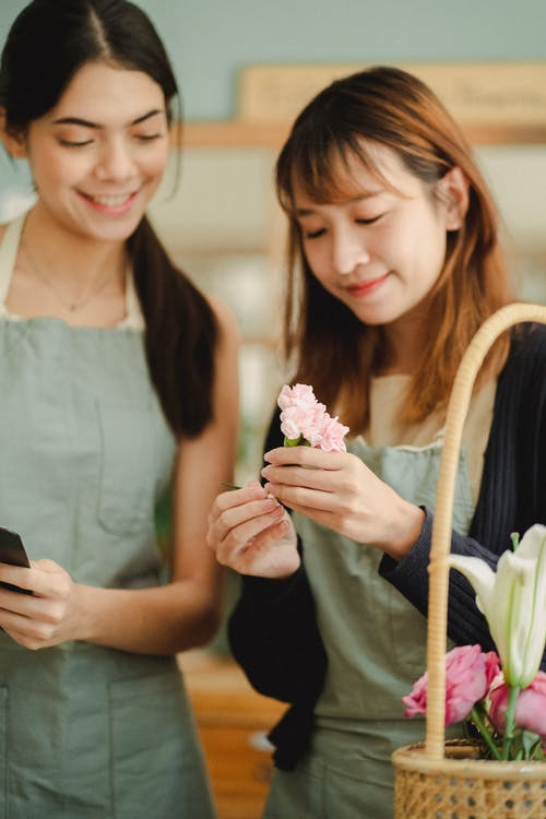 Happy multiethnic female florists wearing aprons and making composition of flowers while creating order during work in floral store with blurred background