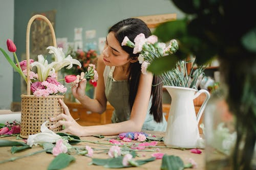 Concentrated female florist standing at table with vase and creating flower composition in wicker basket while preparing order in floristry workshop