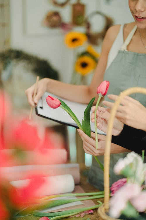 Unrecognizable female coworkers standing at table with tulips and writing notes on clipboard while working in florist atelier with blurred background