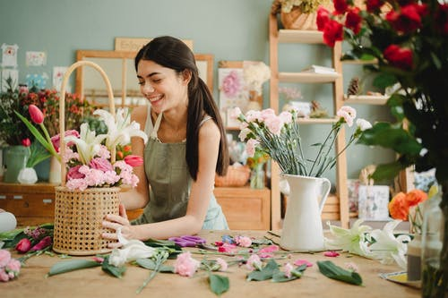 Cheerful woman decorating bouquet in basket