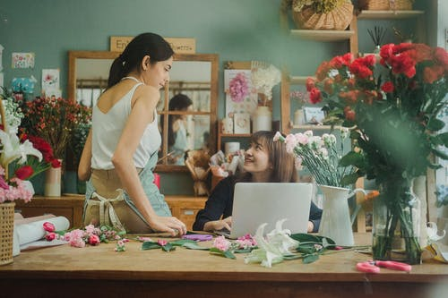 Positive multiracial florists working at table on laptop