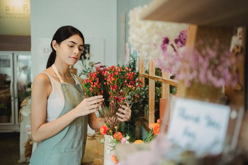 Positive female florist with dark hair making composition of small red flowers while preparing order during work in floristry studio