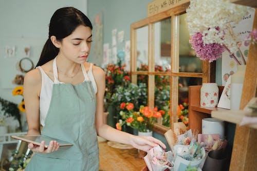 Pensive woman near flowers in wrapper
