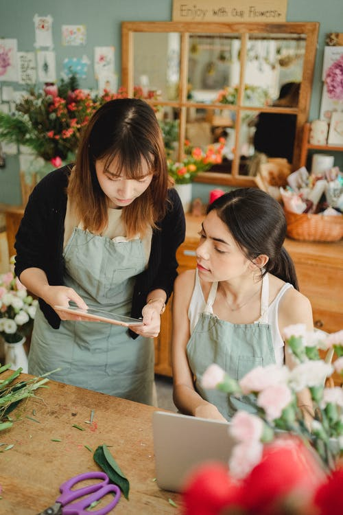 Focused multiracial florists browsing tablet in shop