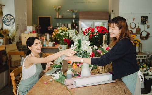 Multiethnic coworkers in floral shop with laptop